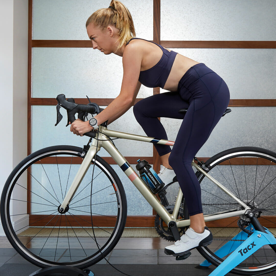Vrouw die aan het wielrennen is op Tacx fietstrainer van Garmin.