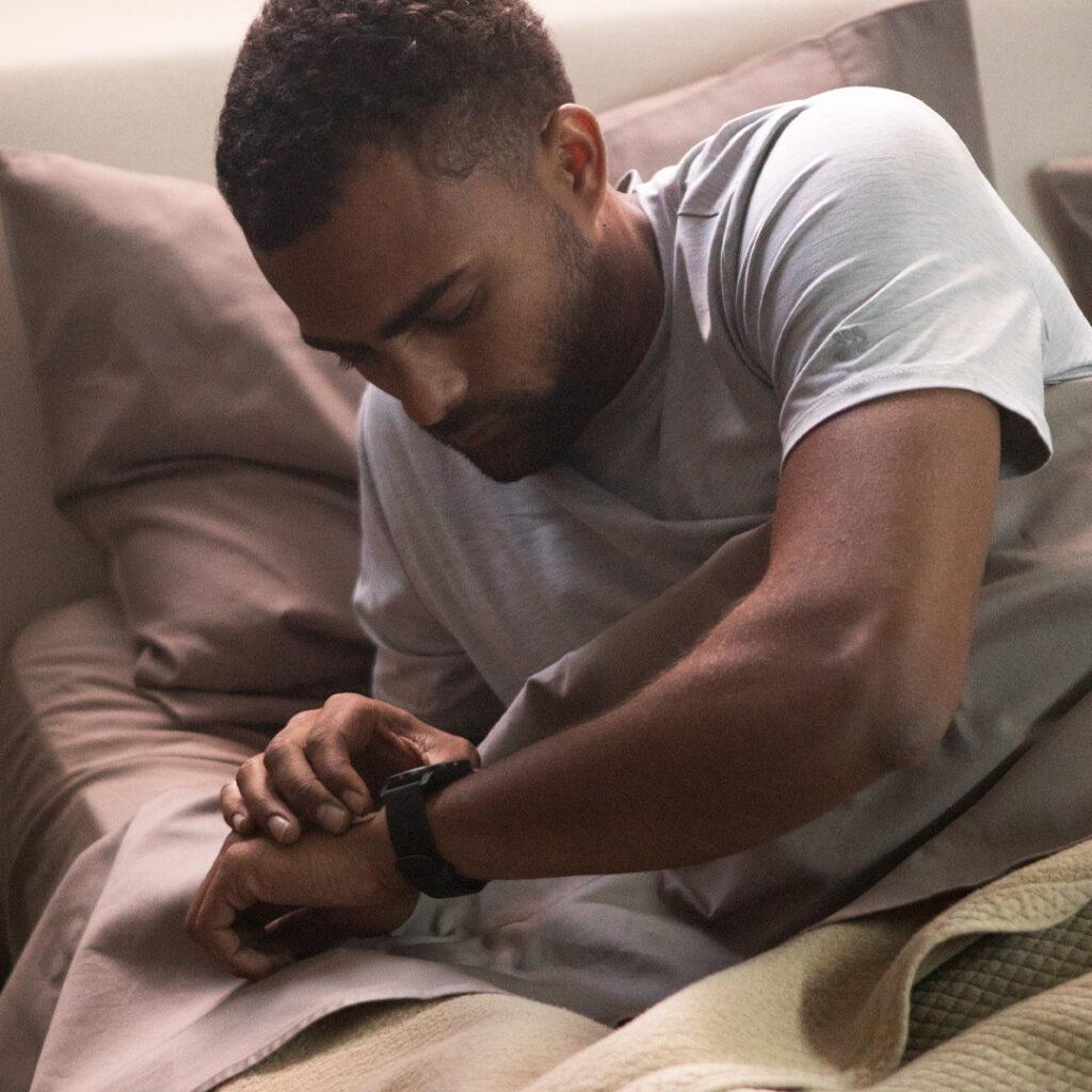 Man in bed die kijkt op Garmin horloge om slaap bij te houden.